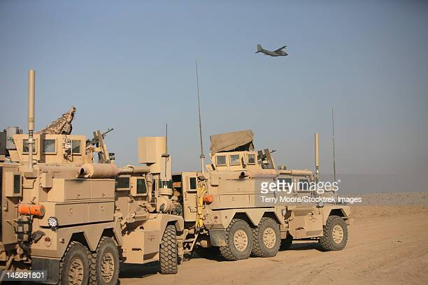 a german transall c-160 flies over two eod cougar armored vehicles. - mine resistant ambush protected stock pictures, royalty-free photos & images