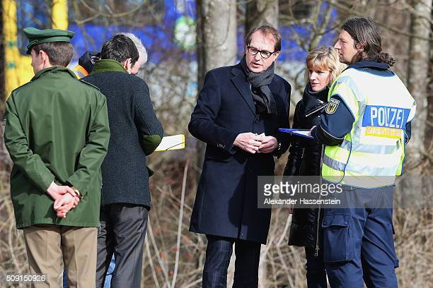 German Transport and Digital Technologies Minister Alexander Dobrindt talks to Police and Rescue workers near the wreckage of two trains that...