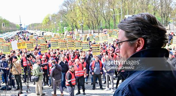 German Transport Minister Andreas Scheuer stands on stage during a protest by Taxi drivers against the German government's plans to liberalize the...