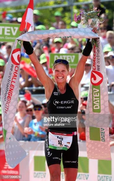 German triathlete Anja Beranek crosses the finish line of the Datev Challenge Roth in Roth Germany 12 July 2015 The participants of the 14th edition...