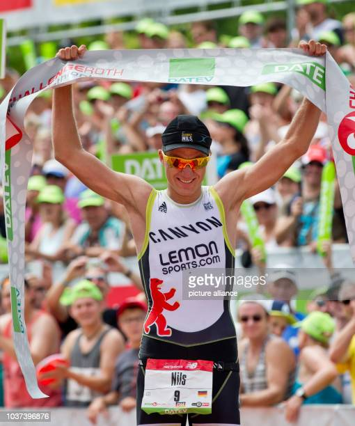 German triathlete Nils Frommhold cheers as he crosses the finishing line to take second place during the Datev Challenge Roth inRoth Germany 20 July...