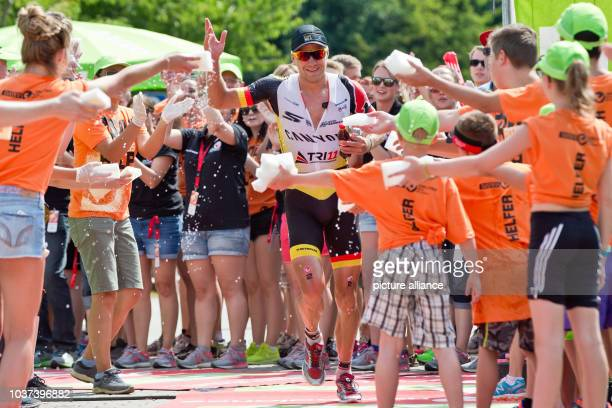 German triathlete Nils Frommhold cools off in the changing zone before starting the marathon stage at the Datev Challenge Roth in Roth Germany 12...