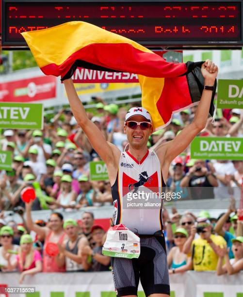 German triathlete Timo Bracht crosses the finishing line to win during the Datev Challenge Roth inRoth Germany 20 July 2014 The competition...