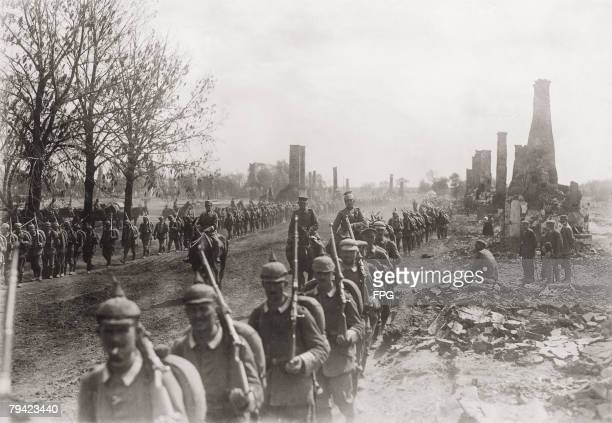 German troops advance past the town of Puchaczow in East Prussia burnt down by retreating Russian forces on the Eastern Front during World War I...