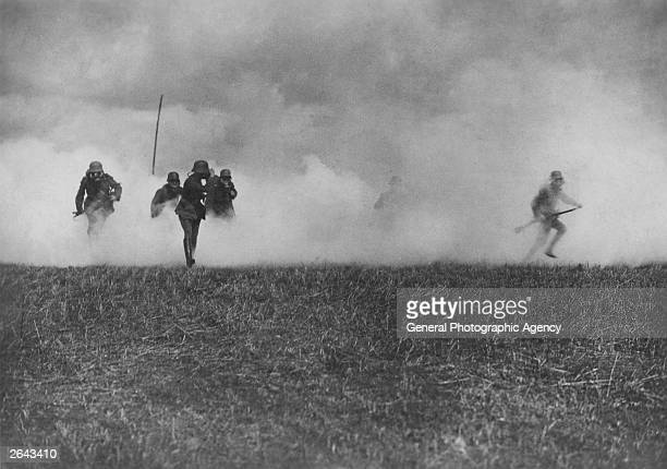 A German officer leads his men through a cloud of phosgene gas set off by themselves for cover as they run toward the British trenches circa 1916