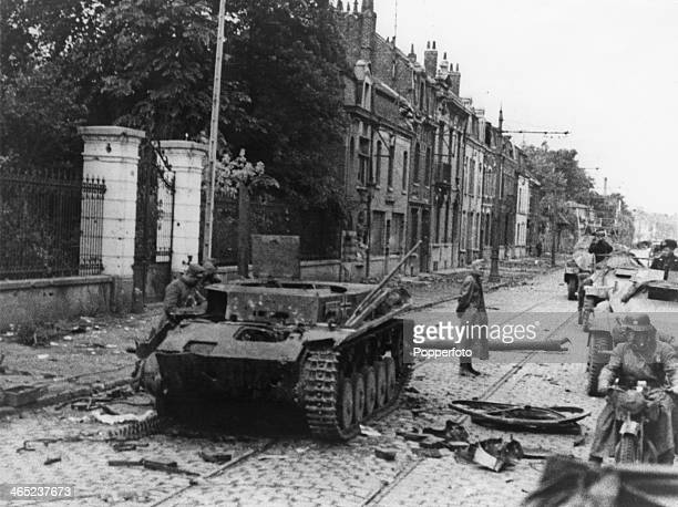 German troops pass a knocked-out German tank as they enter Lille after the siege of the city, France, May-June 1940.