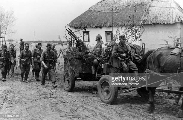 German troops passing by an hut with an antiaircraft gun during Kharkiv's battle Kharkiv May 1942