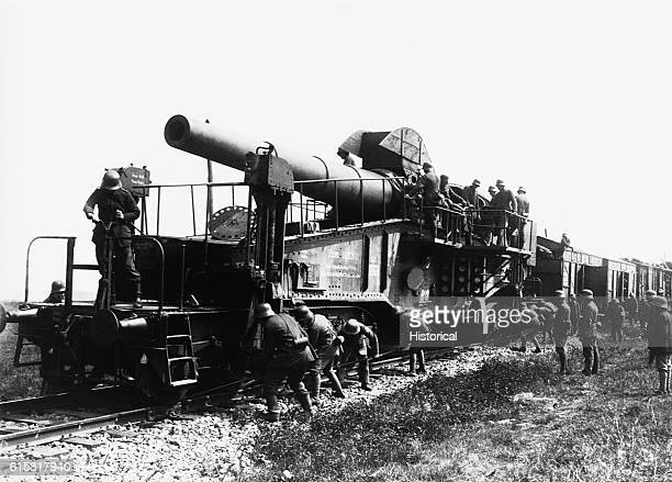 German troops set the azimuth for horizontal lay on a 28 cm rapid firing gun mounted on a train