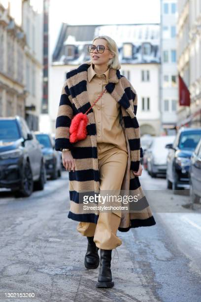 German TV and radio host Verena Kerth wearing a long beige and black striped coat by Max Mara, a red bag by Chanel, a beige leather shirt by Ganni,...