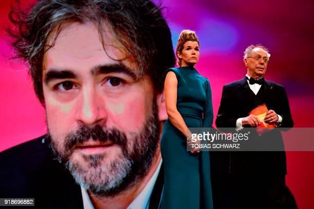 German TV host Anke Engelke and Berlinale Director Dieter Kosslick stand on stage in front of a portrait of German journalist Deniz Yucel held in...