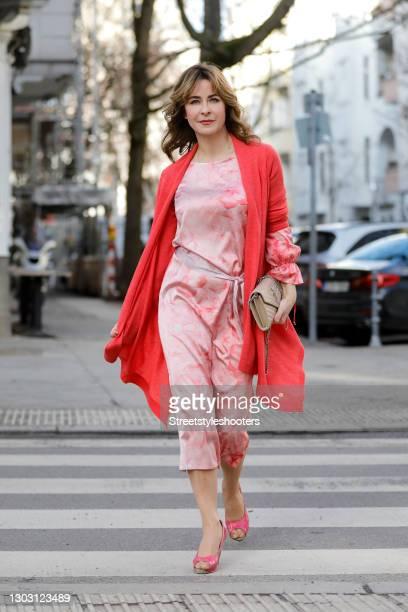 German TV host Bettina Cramer wearing a light pink floral print dress by Anja Gockel, a pink long knitted cardigan by Anna von Griesheim, a beige bag...
