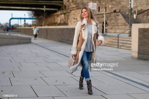German TV host Frauke Ludowig wearing a silver shirt by Sportalm, a long brown and cream colored fur coat by Sportalm, blue acid wash denim jeans, a...