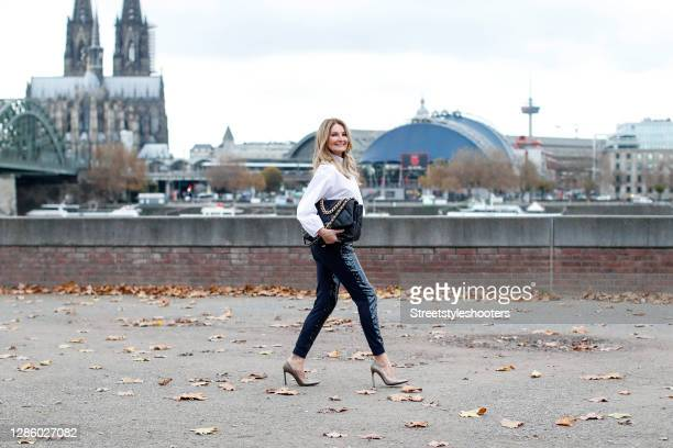 German TV host Frauke Ludowig wearing a white blouse by Ancora, black sequin pants by Ancora, a black and gold bag by Chanel and gold pumps by Stuart...