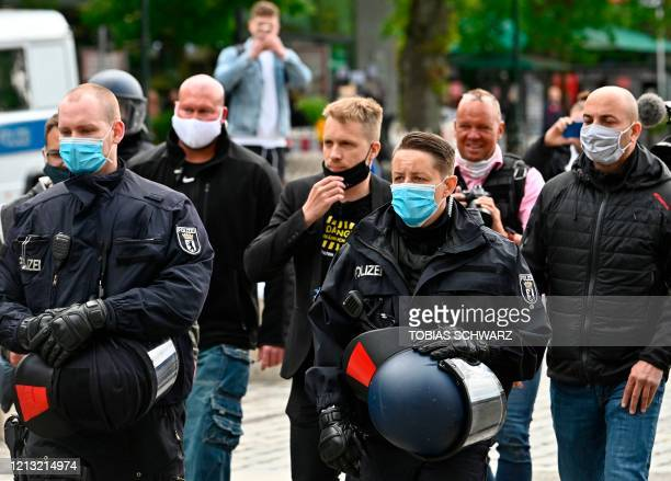 German TV host Oliver Pocher is escorted by police on the sidelines of a protest against restrictions implemented in order to limit the spread of the...