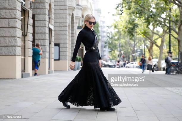 German TV host Tamara von Nayhauss wearing a black hip bag by Carlo Colucci, a black maxi skirt with cut outs by Dawid Tomaszewski, a black...