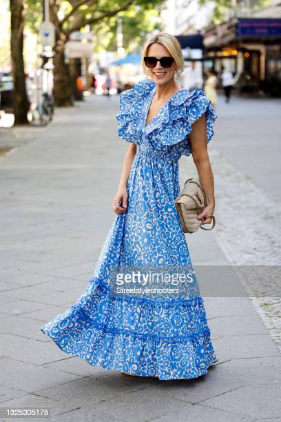 German TV host Tamara von Nayhauss wearing a blue and white summer maxi dress with floral print and ruffle detail by Mooi Berlin, cream colored mules...