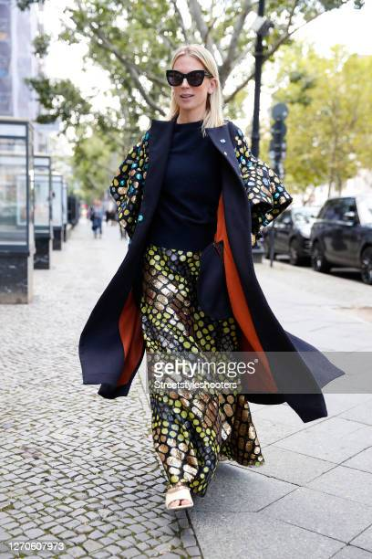 German TV host Tamara von Nayhauss wearing a dark blue coat with multicolored sequin and burned orange lining by Dawid Tomaszewski, a maxi skirt with...