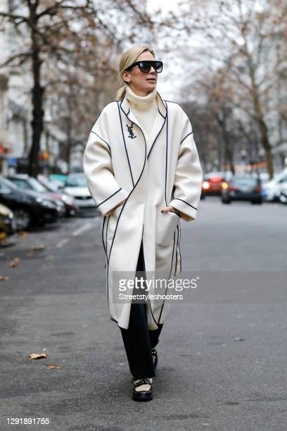 German TV host Tamara von Nayhauss wearing a long cream colored coat by Yves Saint Laurent, black and beige shoes with studs and faux fur details by...