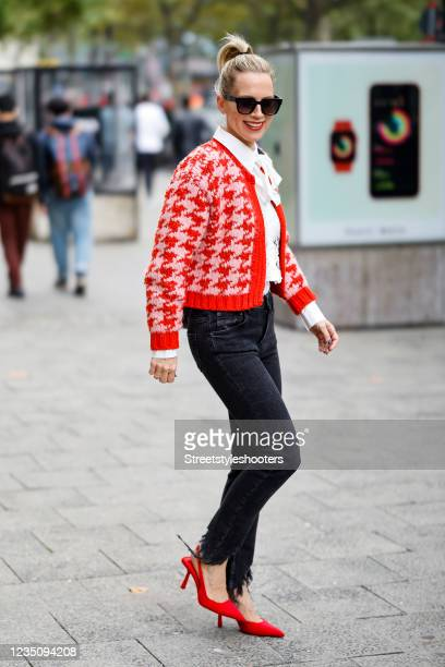German TV host Tamara von Nayhauss wearing a white floral lace lavalliere blouse by Zara, a red and pastel pink knitted houndstooth pattern cardigan...