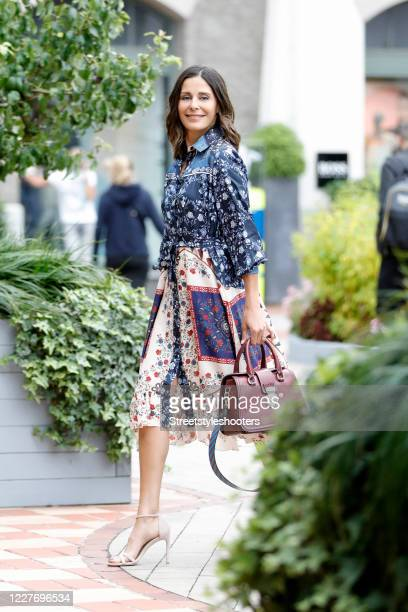 German tv presenter and actress Funda Vanroy wearing a blue, red and beige midi length dress with floral print by Sandro, nude sandals by Stuart...