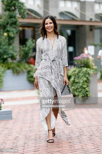 German tv presenter and actress Funda Vanroy wearing a white dress with black dots by Ingolstadt Village, black sandals by Stuart Weitzman and a...