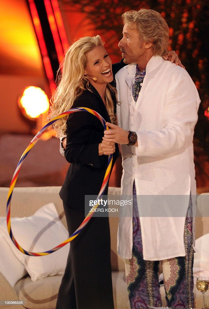 German tv-host Thomas Gottschalk and his co-host Swiss model Michelle Hunziker joke during the television show 'Wetten, dass..?' (Let's Make a Bet) at the 'Coliseo Balear' bull fighting arena in Palma de Mallorca on the Balaeric Island of Mallorca on May 23, 2010.
