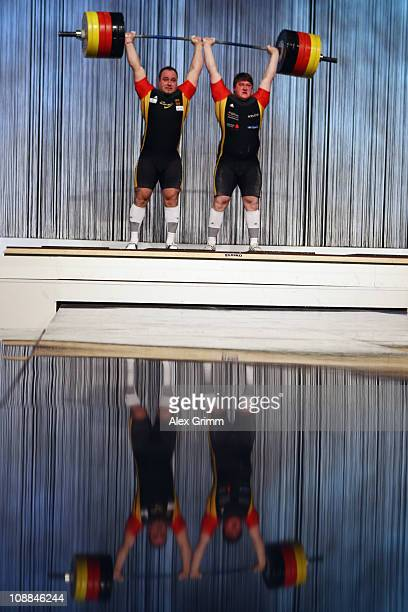 German weightlifters Almir Velagic and Matthias Steiner are reflected in the stage floor during preperations to set a new world record lifting a...