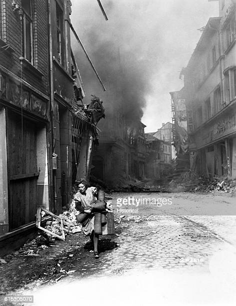 A German woman carrying a few possessions runs from a building in Seigburg Germany which was set on fire by a Nazi saboteur April 13 1945 | Location...