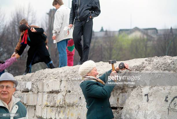German woman having fun by trying to pull down the Berlin Wall using a hammer Berlin 1989