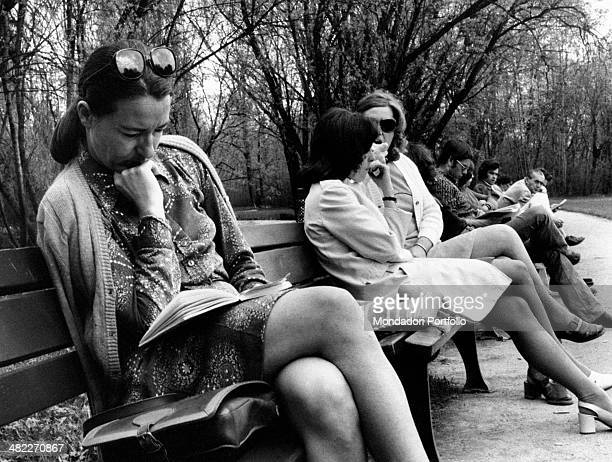 A German woman reading a book sitting on a bench at the park Hamburg 1973