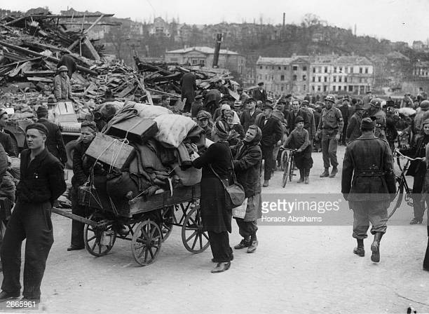German women in Saarbrucken the capital of the Saar push a cart piled with belongings through the devastated streets towards a communal centre...