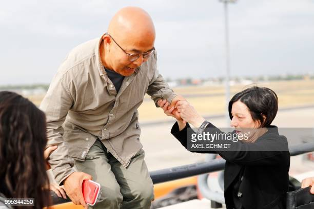 German writer and Nobel Literature Prize laureate Herta Mueller helps Chinese dissident and writer Liao Yiwu down from the viewing platform after the...