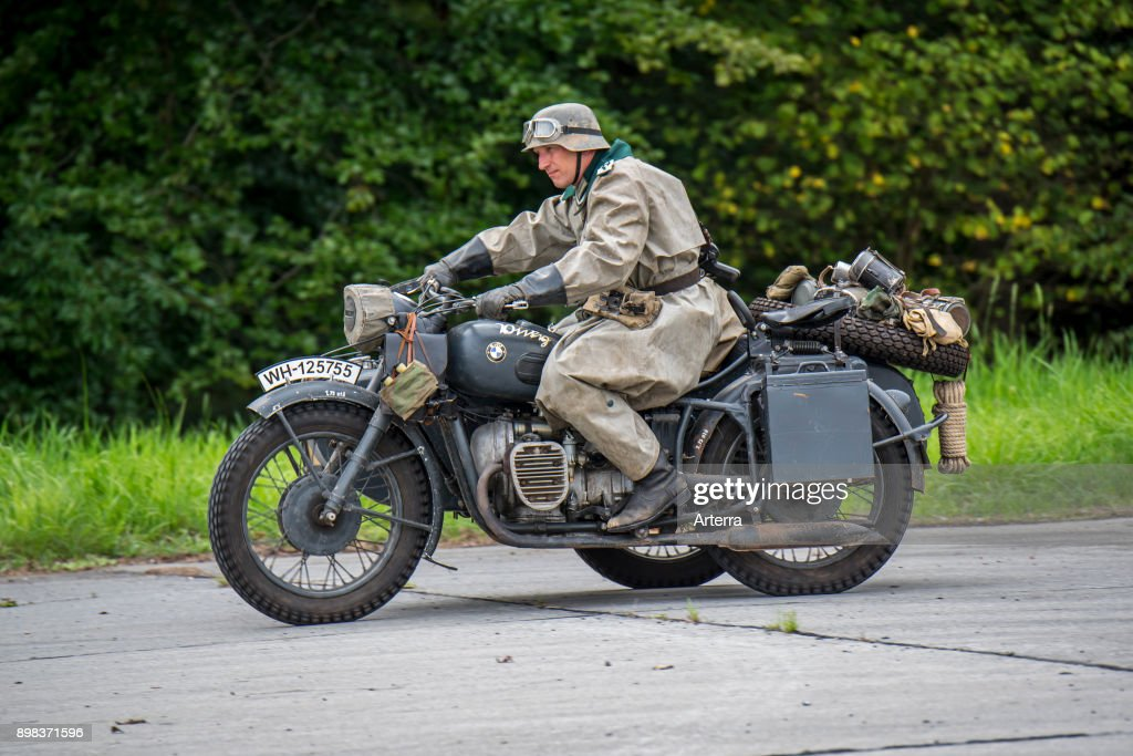 German WW2 soldiers riding on BMW military motorcycle with sidecar