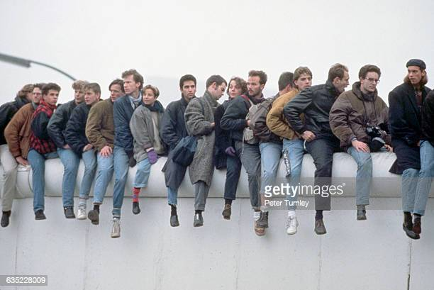 German youths sit atop the Berlin Wall during its Fall