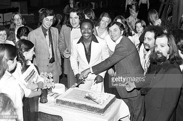 GermanAmerican music promoter Bill Graham cuts a birthday cake for American guitarist and singersongwriter George Benson San Francisco March 1977