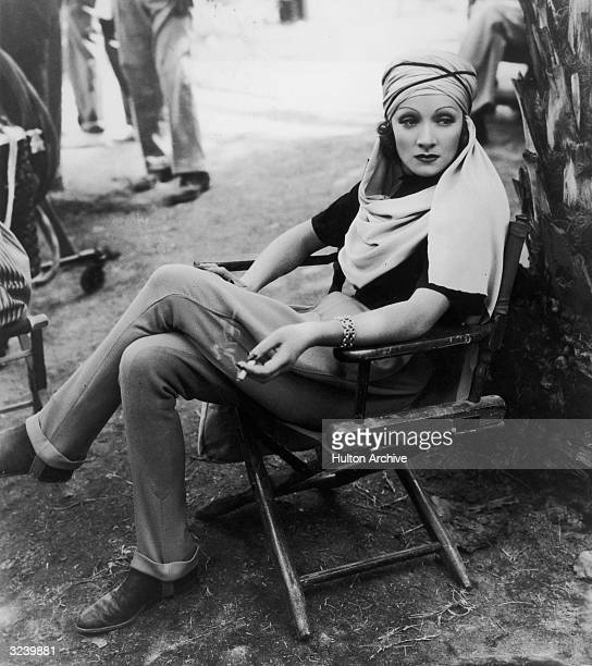 Germanborn actor Marlene Dietrich sits in a canvas chair wearing a turban and holding a cigarette on the desert location set of director Richard...