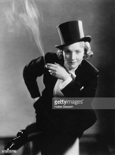 Germanborn actress and singer Marlene Dietrich smokes a cigarette wearing top hat and tails in a risque portrait from the 1930s Dietrich moved to the...