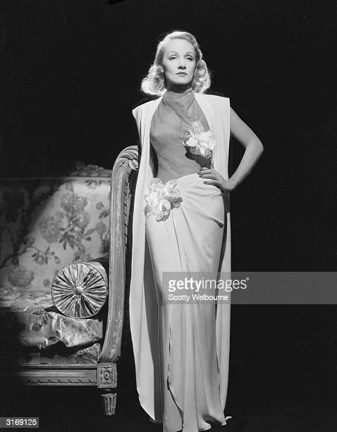German-born actress Marlene Dietrich looking exquisite in a white gown and elegantly draped skirt.