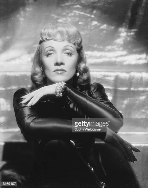 German-born actress Marlene Dietrich wearing a dark satin gown and curled fringe for the film 'Manpower'. Costumes by Milo Anderson.