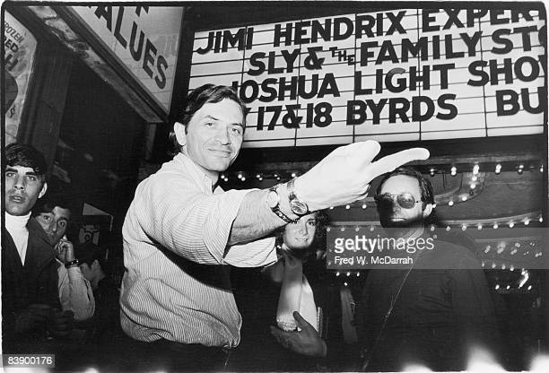 German-born America concert promoter Bill Graham smiles as he extends his middle to the camera while he, and assorted patrons, stand under the...
