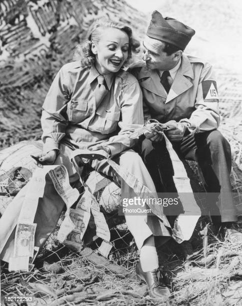 Germanborn American actress and singer Marlene Dietrich and songwriter Irving Berlin compare 'short snorters' at a Fifth Army Mobile Radio Station...