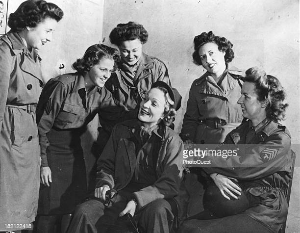 Germanborn American actress and singer Marlene Dietrich chats with a group of WACs at the headquarters of the 12th Army Group during a tour for...