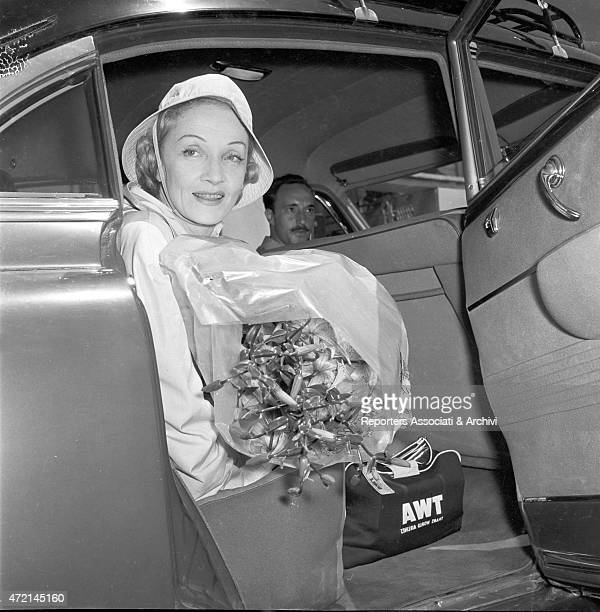 'Germanborn American actress Marlene Dietrich getting into a car with a big bunch of flowers after landed at Ciampino airport Ciampino 1957 '