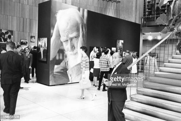 Germanborn American photographer Alfred Eisenstaedt stands at the bottom of a staircase in the Time Life Building during an exhibition of his work...