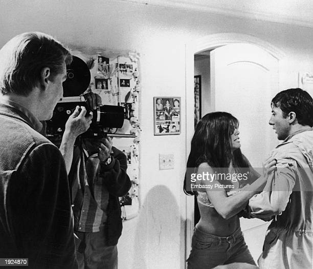 Germanborn director Mike Nichols watches as American actors Katharine Ross and Dustin Hoffman act in front of a movie camera on the set of Nichols's...