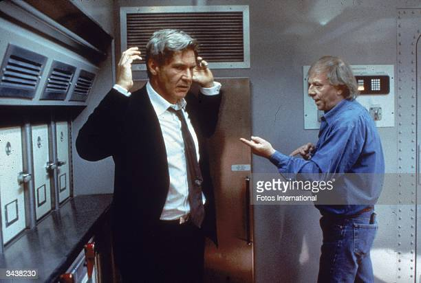 Germanborn director Wolfgang Petersen instructs American actor Harrison Ford on the set of Peterson's film 'Air Force One'