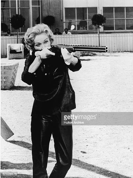 Germanborn film actoress Marlene Dietrich aims a shotgun on a shooting range early 1950s She is dressed in leather pants and a leather jacket and...