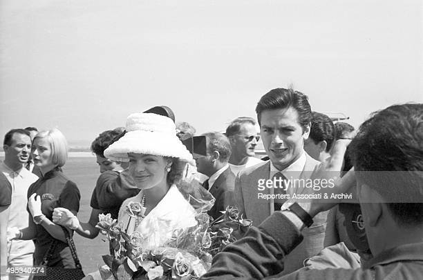 Germanborn French actress Romy Schneider and French actor director and singer Alain Delon greeting the reporters at Cannes airport The actors will...