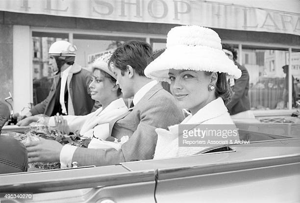 Germanborn French actress Romy Schneider Italian actress and singer Sophia Loren and French actor director and singer Alain Delon greeting their fans...
