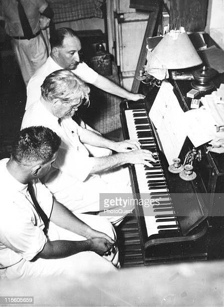 Germanborn French medical missionary and theologian Dr Albert Schweitzer plays the piano at his home as unidentified other listen Lambarene Gabon May...